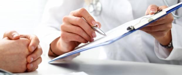 Ärztin zeigt Patientin etwas auf einer Schreibunterlage